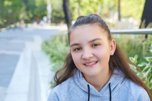 Девушка подростка ребенка с рюкзаком сидит и улыбается. онлайн-обучение, дистанционное обучение, домашнее обучение.