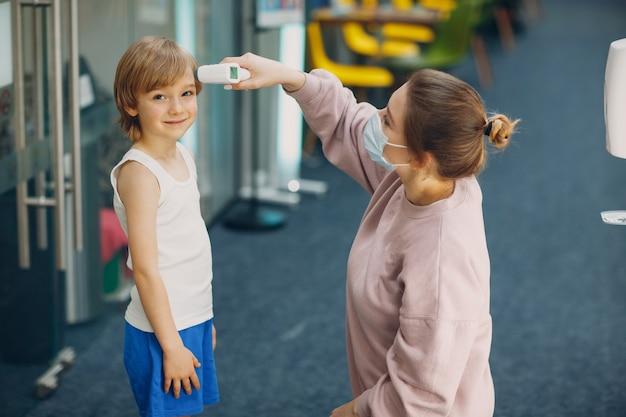 幼稚園のレーザー体温計による子どもの体温測定女性