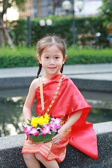 Child in thai traditional dress with krathong for forgiveness goddess ganges festival in t