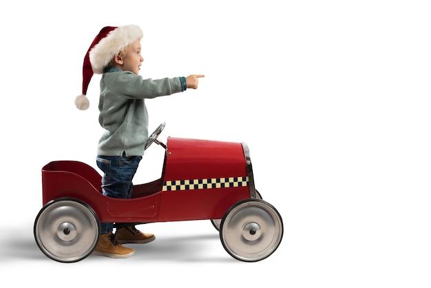 おもちゃの車で遊ぶ子供がサンタクロースを待つ