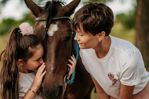 馬との散歩のための子供の治療。馬との感情的な接触。夏の公園で母娘を馬と散歩。