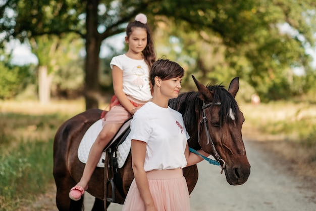 Child therapy for a walk with a horse. emotional contact with the horse. walk mother and daughter in the summer in the park with a horse.