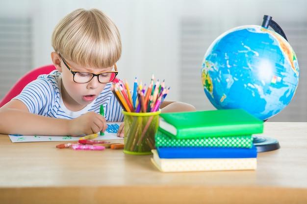아이는 배우기 힘들다. 불행한 학생. 작은 남학생을 지쳤다. 교실에서 소년. 숙제를하는 아이.
