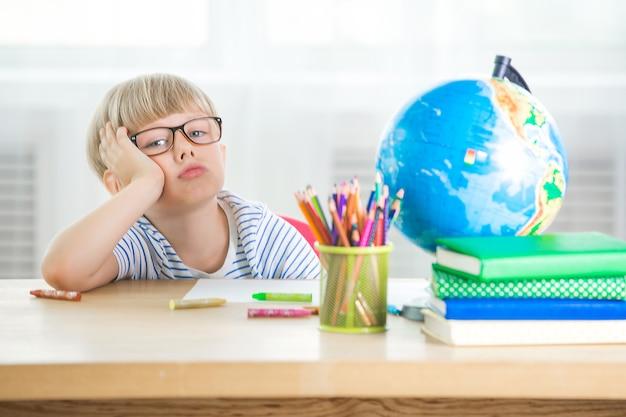 Ребенку надоело учиться. несчастный студент. измученный маленький школьник. мальчик в классе. малыш делает домашнее задание.