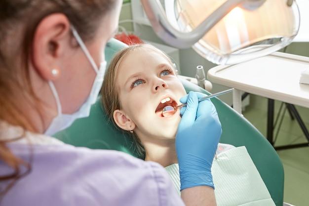 歯科医への子供。手術中の歯科治療椅子の歯科治療中の子供。歯科医院の専門医を訪問している小さな子供の患者。