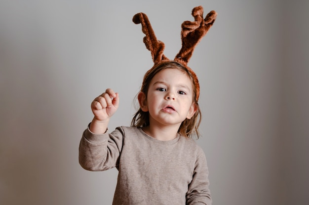 Child toddler with deer headband at home with exited funny face. christmas new year holidays