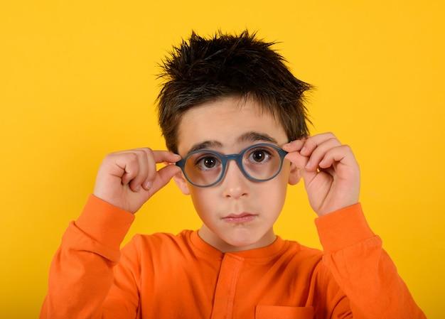Ребенок пробует новые очки, чтобы лучше видеть на желтом