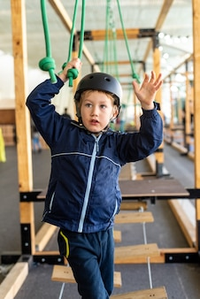 Child trying to overcome the obstacles of an adventure park.