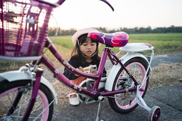 Ребенок пытается починить свой собственный велосипед