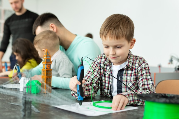 Child using 3d printing pen. boy making new item. creative, technology, leisure, education concept