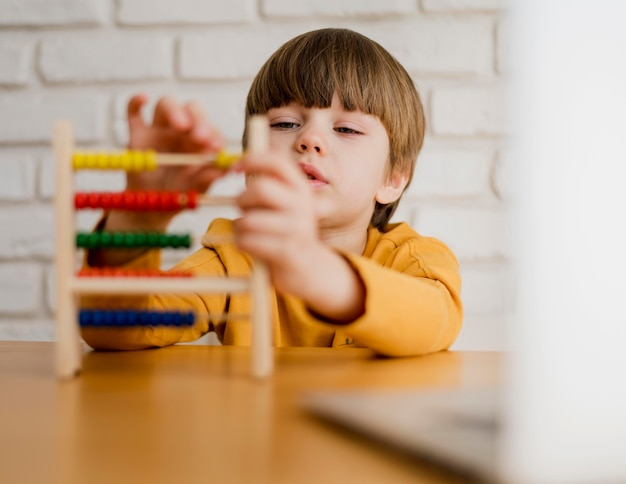 Child using abacus at home with laptop