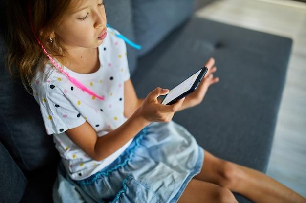 モダンで明るいアパートのソファで携帯電話を使用している子供、若い女の子は自宅でスマートフォンで遊ぶ、ガジェット中毒の問題