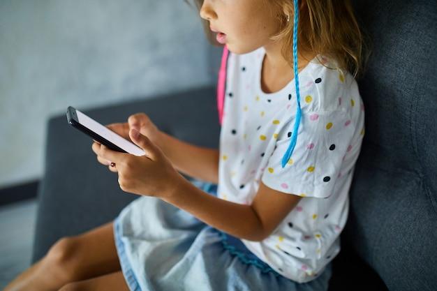 현대적이고 밝은 아파트의 소파에서 휴대폰을 사용하는 어린이