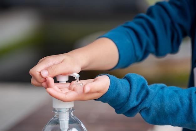 手の消毒剤を使用する子。