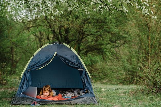 テントの中でラップトップを使用している子供