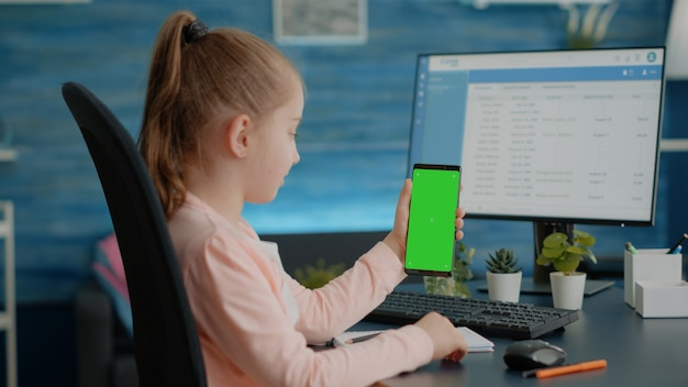 Child vertically holding smartphone with green screen