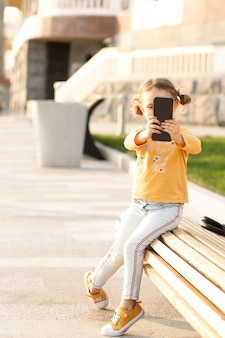 Child vlogger making video call,chatting with friends outdoor.kid tourist blogger making selfies photo for social networks on phone next to tourist attraction point.quarantine over.coronavirus ended