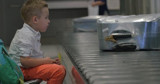 手荷物受取所で待っている子供