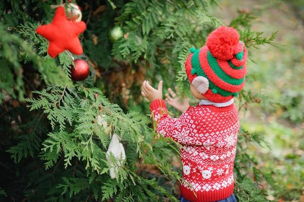 木のクリスマスを待っている子。ツリーの近くの小さな男の子の肖像画。赤ちゃんを飾る松。冬の休日と人々の概念。メリークリスマスとハッピーホリデー