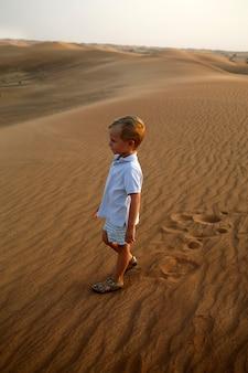 어린이가 사막의 모래에서 걷고 발자국을 남기고, 작은 관광객이 세계를 탐험하고, 아이들과 함께 여행합니다.