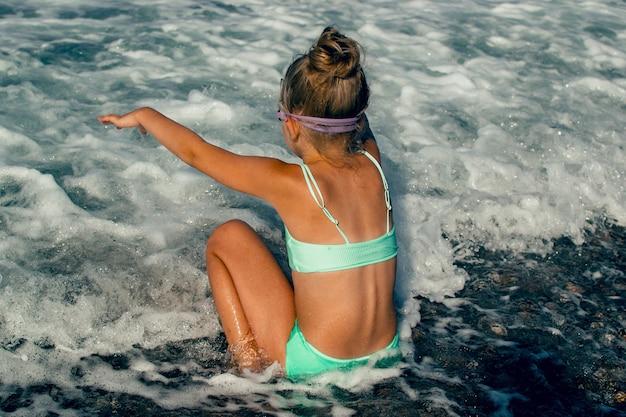 Ребенок гуляет и играет на берегу моря в купальнике