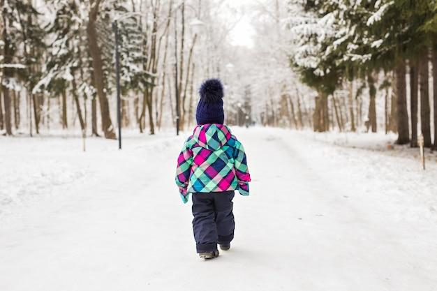 Ребенок уходит в лес в зимний день.