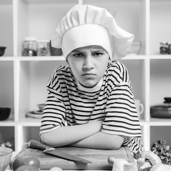Child want to be a professional chef confident little chef at the kitchen boy wearing chef hat