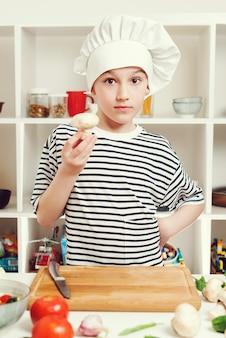 子供はプロのシェフになりたいです。家族の夕食のために健康的な食事を準備しているシェフの少年。シェフの帽子と制服を着たかわいい男の子。料理のコンセプト。家庭の台所で料理をしている小さなシェフ。