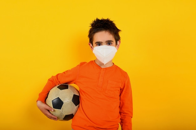 Child wants with face mask for covid-19 coronavirus wants to play at soccer on yellow