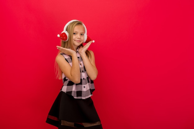 A child in a warm ear muffs on a red background. the concept of winter, christmas, new year.