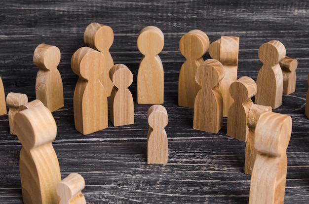 The child was lost in the crowd. a crowd of wooden figures of people surround a lost child