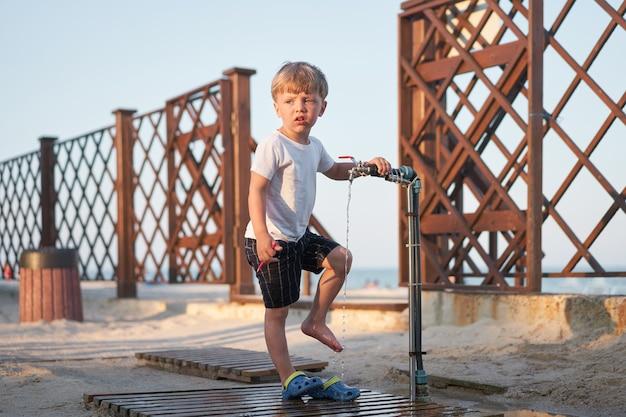 ビーチ砂の後に足を洗う子供白人の男の子がビーチに立っています。子供の頃の夏。子供1人との家族旅行。