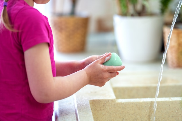 Child washes his hands with soap at home. concept of protection from viruses.
