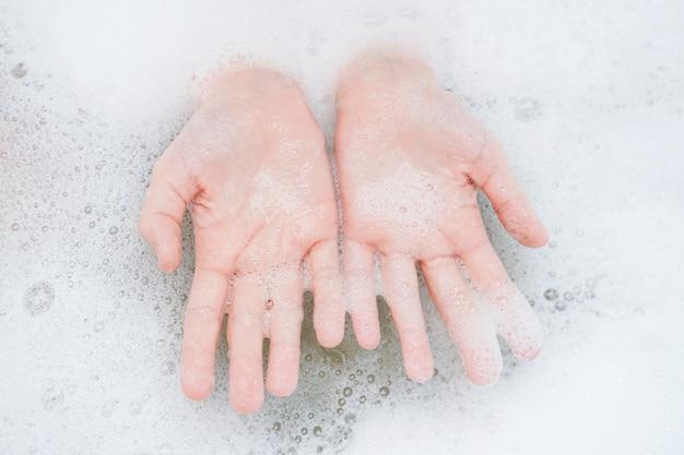 Child washing hand in bathroom.