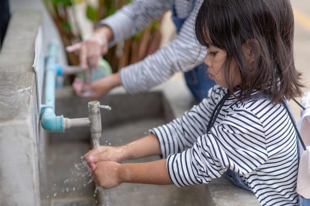 石鹸で手を洗う子供