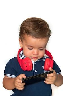 赤いヘッドフォンと紺色のシャツを着て携帯電話でビデオを見ている子供