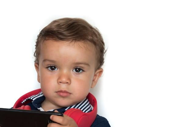 빨간 헤드폰과 진한 파란색 셔츠와 함께 휴대 전화에서 비디오를 보는 어린이
