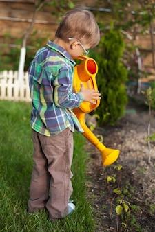 뒤뜰에 있는 정원에 물을 주는 아이
