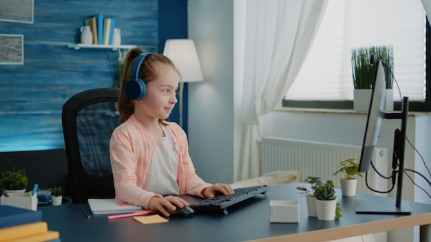 Ребенок машет на веб-камеру видеозвонка на компьютере для школьной работы