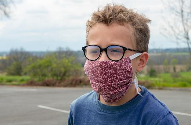 Ребенок в антивирусной маске на открытом воздухе