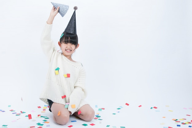 The child wearing a black party hat is having fun. white background and black hat go well together.