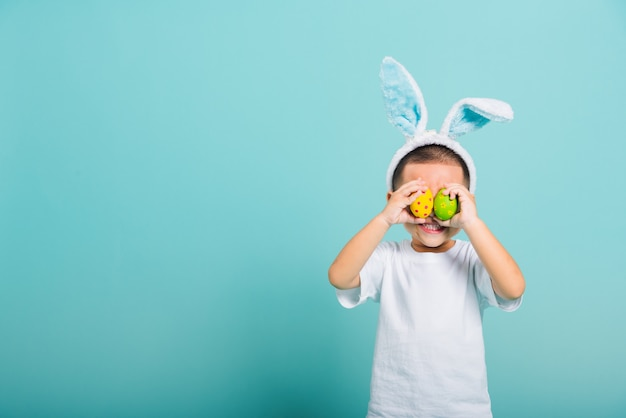 Child wearing bunny ears standing holds easter eggs instead of eyes