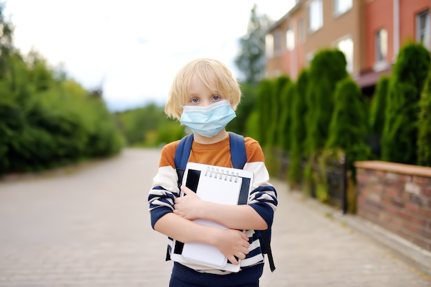 Ребенок в маске для лица собирается в повторно открыть школу