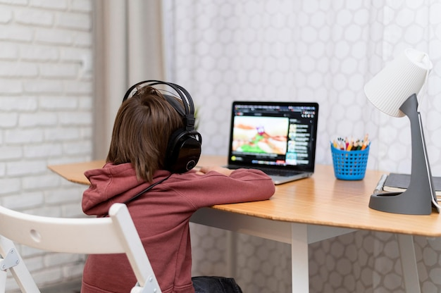 Child wearing headphones attending online courses