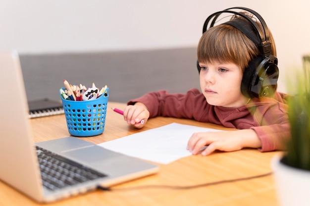 온라인 학교에 다니는 헤드폰을 착용하는 어린이