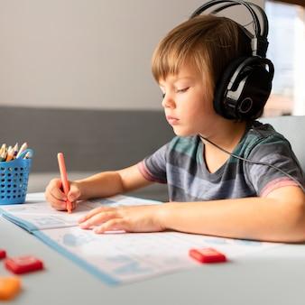 가상 수업에 참석하는 헤드폰을 착용하는 어린이