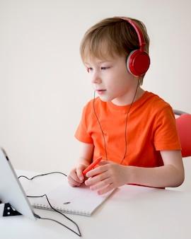 Child wearing headphones on an online class