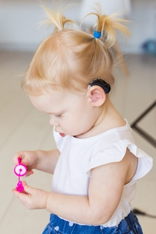 Child wearing a hearing aid at home