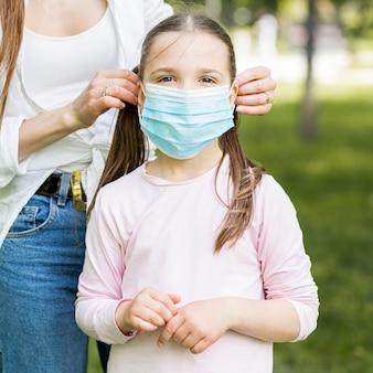 Ребенок носит медицинскую маску для защиты