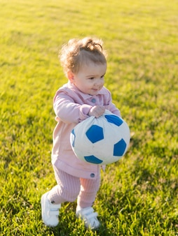 Child wearing pink clothes playing with ball
